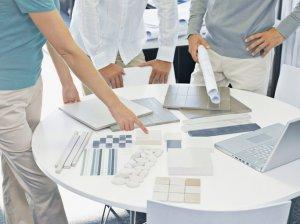 trzy osoby analizujące projekt architektoniczny